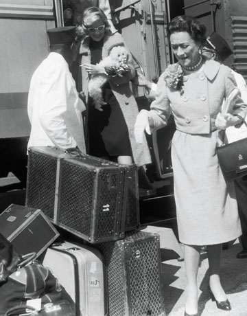 1956: EXCLUSIVE Wallis Simpson, the Duchess of Windsor, stands next to luggage on a train platform with porters, Florida. (Photo by Morgan Collection/Getty Images)